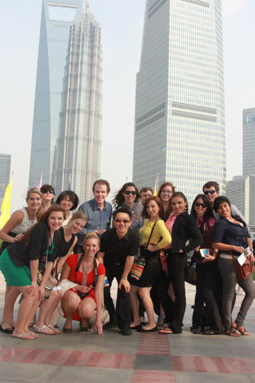 The study abroad group takes a quick photo in front of Shanghai skyscrapers.